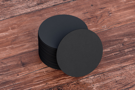 Black round beer coasters on wooden background  around coasters. 3d illustration