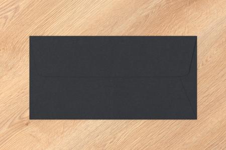 Black blank closed envelope on wooden background. 3d render