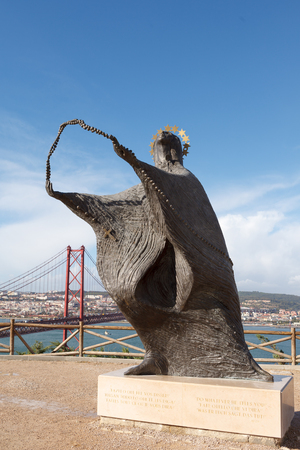 The statue of the Virgin Mary and the view of the 25th of April Bridge in front of  Santuario Nacional de Cristo Rei. Lisbon, Portugal