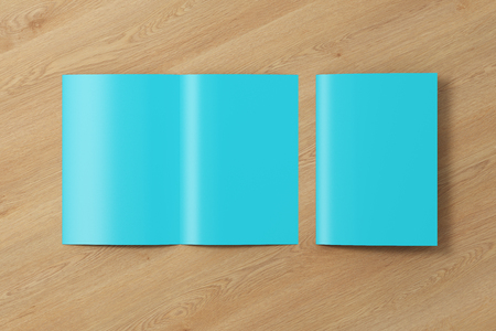 Blank cyan open and folded half-folded flyer leaflet on wooden background. 3d illustration