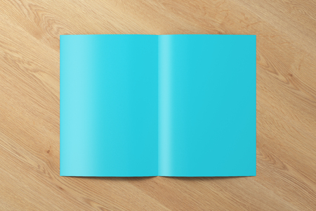 Blank cyan half-folded flyer leaflet on wooden background.