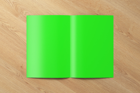 Blank green half-folded flyer leaflet on wooden background.