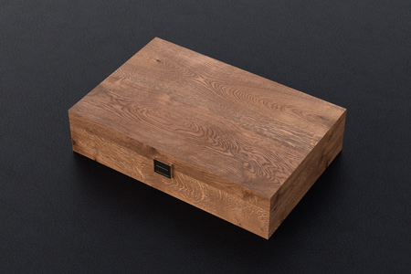Dark wooden closed long box or casket on black background. 3d illustration