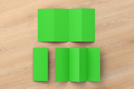 Blank green folded paper leaflet on wooden background. Eight pages, four panel. 3d illustration