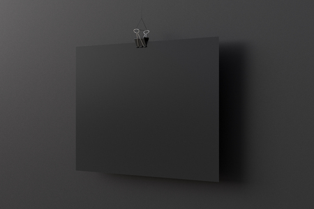 Blank horizontal black paper poster hanging on binder clip on black wall background. 3d illustration Фото со стока