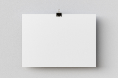 Blank horizontal paper poster hanging on binder clip on white wall background. 3d illustration Фото со стока