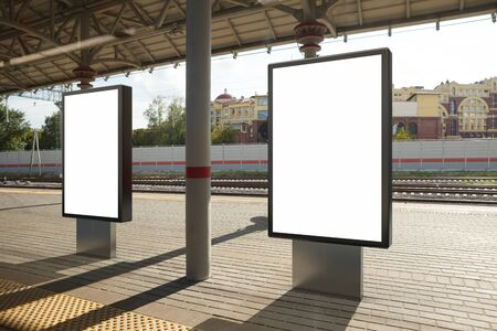 Two blank billboard poster stands mock up on platform of raillway station. 3d illustration.