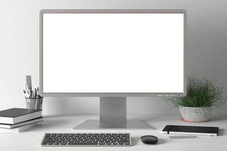 Werkruimte met blanco computermonitor wit scherm mock-up op het witte bureau in de buurt van witte muur. toezicht houden op; scherm; computer; bespotten;