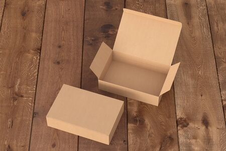 Blank cardboard wide flat box with open and closed hinged flap lid on dark wooden background. 3d illustration