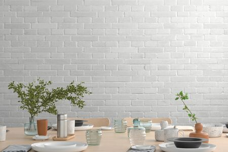 Blank white brick wall mock up in the dinning room with served table. 3d render