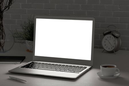 Workplace with glowing laptop screen at evening mock up.  White desk and brick wall. Side view. Clipping path round laptop screen. 3d illustration