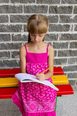Girl draws on the album sitting bench photo