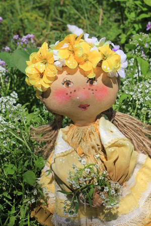 woman hanging toy: Russian homemade rag doll as symbol of summer