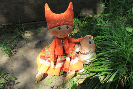woman hanging toy: Russian homemade rag doll as symbol of autumn