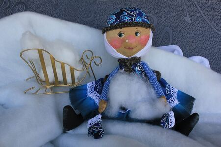 woman hanging toy: Russian homemade rag doll as symbol of winter