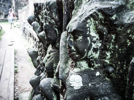 Detail of the wall of the ancient Angkor Thom Bayon Temple in the Angkor Area, near Siem Reap, Cambodia, Asia. Buddhist monastery from the 12th century. Asian architectural background.