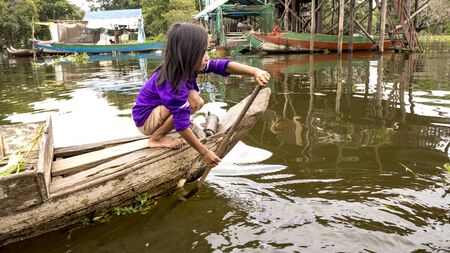 TONLE SAP LAKE, SIEM REAP PROVINCE, CAMBODIA - 23 NOVEMBER, 2017: little girl is moving around the lake in wooden boat Archivio Fotografico - 133363279