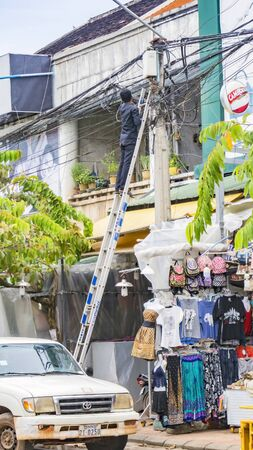 SIEM REAP, CAMBODIA - NOVEMBER 13, 2017: electrician standing on ladder and working, repairing system of electric wire Editorial