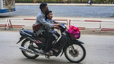POIPET, CAMBODIA -  NOVEMBER 24, 2017:  Two riders: crying Asian little boy, kid with adult man on the scooter  motorbike. The border crossing between Thailand and Cambodia.