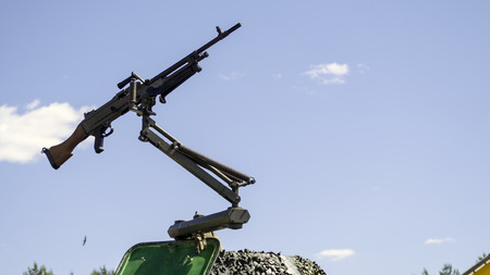 machine gun mounted on a military vehicle, army gun isolated on the blue sky background
