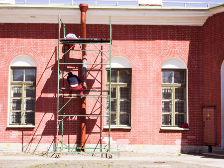 Construction and repair of a publik brick house. long building ladder and scaffolding, restoration work of old building in Russia