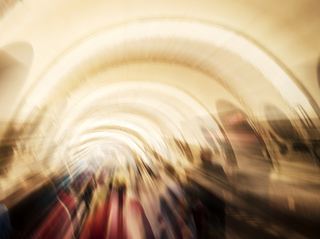 Blurred Silhouettes in tunnel, going towards the light. People. walking through a lit corridor, which conveys the concepts of rebirth. Bright light at the corridor end, the concept of clinical death.