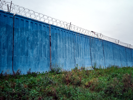 barbed wire steel blue wall against the sky. Concrete wall, against the backdrop of barbed wire, the concept of prison, salvation, Refugee, lonely, space for text