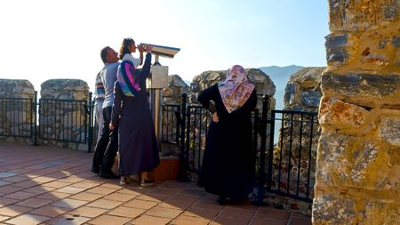 KONAKLI, ALANYA - 06 JULY 2018: arab family of tourists on viewing platform with binocular near fortress wall overlooking  sea. Back view. Summer vacation concept. Copy space. Blue sky and mountains Editorial