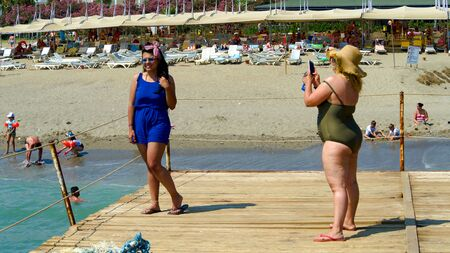 KONAKLI, ALANYA, TURKEY - 06 JULY 2018: beautiful european tourists are taking photo near beach on pier overlooking the sea. Back view. For Alanya in Turkey. Summer vacation concept. Copy space.