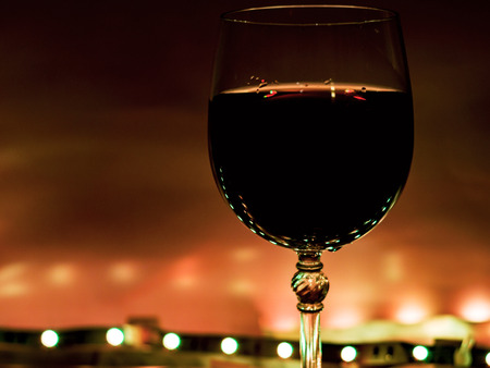 Closeup of glass of wine on the black background with Christmas decoration -bright lights. Traditional winter holiday alcohol with creative New Year artwork. Copy space. blurred or bokeh lights. Stock Photo