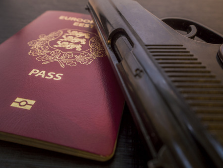 Close up of passport of the European Union (EU) and Estonia and handgun. Dark business and Traffickers international crime concept on black background. Illegal crossing of the state border. Illegal. Banco de Imagens