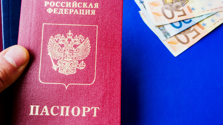 Image of a persons hand holding Russian passport on the blue textile background . and Euro banknotes. citizenship of russia - Russian Federation. Top view. Copy space for text or design.