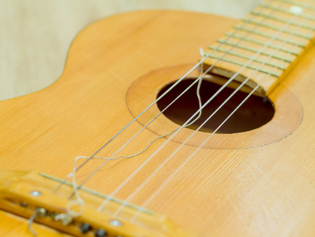 Old classical guitar with broken Strings. On the wooden background