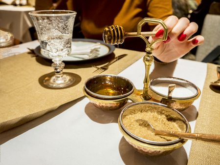 Close up of womans hands taking honey in a restaurant at the table. honey and honey dipper,  salt and sugar background.