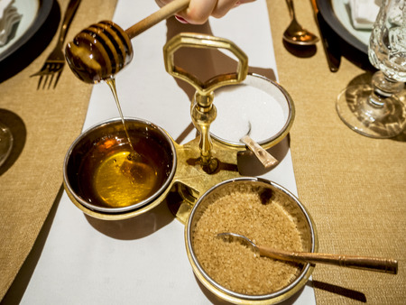 Close up of womans hands taking honey in a restaurant at the table. honey and honey dipper,  salt and sugar background.  Copy space fot text box and design