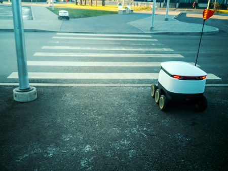 Two moving delivery robots on the street. crossing the road with a pedestrian crossing. cyber-couriers are already cruising the sidewalks in Estonia (Tallinn) are cruising the sidewalks