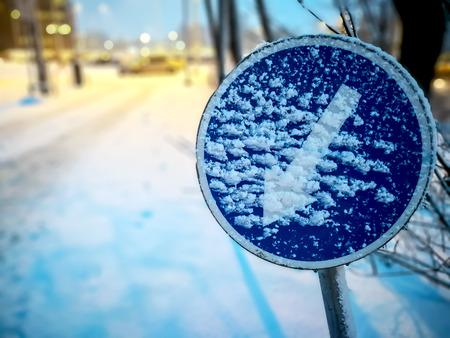 Warning traffic sign. Frozen Road ice-covered direction sign detour on the left. Snowy frozen roads in winter Stockfoto