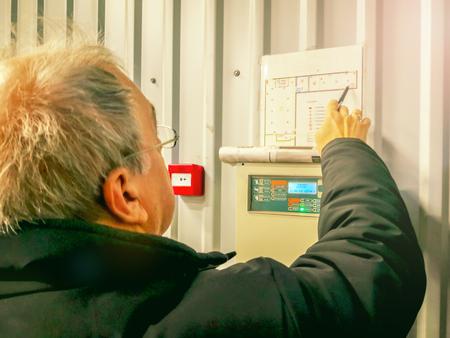 anziano ingegnere riparatore caucasico del sistema di allarme antincendio. Ispezione e test del pannello di allarme antincendio. tecnico sul lavoro che controlla i progetti Archivio Fotografico