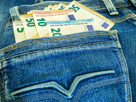 Euro Money notes in blue denim jeans back pocket. Amount of money concept banner for web, giftcard, postcard. Concept of wealth, saving or spending money. Euro bills falling out. copy space, top view