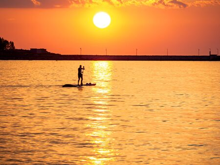 Sunset Silhouette of summer surfing Man Standing on paddle board . Sunset and orange sun rays in summer day. Paddling on the quiet sea, . SUP. For desktop, wallpapers, banner. Copy space, text box.