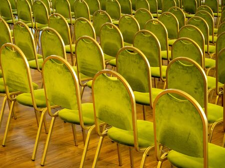 Scene at conference hall with lots of golden and green chairs for attendee to sit and wooden podium and classic curtains Stock fotó
