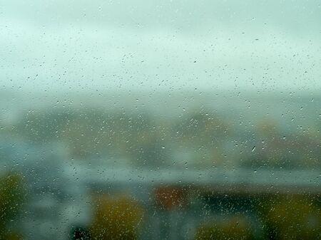 Regentropfen auf Fenster mit grünem Wald im Hintergrund. Nasses Fensterglas. Regentropfen hautnah. Standard-Bild