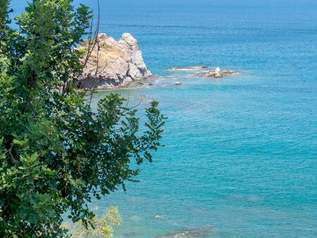 The beach of Aphrodite is the famous tourist destination, Cyprus. Amazing Seascape with blue sea, cliffs and trees Stok Fotoğraf