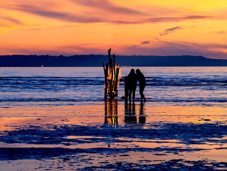 People silhouettes, Large Fire Brightly Burning at night and Rippling golden water of ocean at the orange sunset