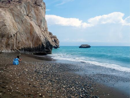 Young beautiful girl take photo on the Love beach. Aphrodites Rock is a birthplace near Paphos City. The rock of the Greek - Petra tou Romiou. Cyprus island Banque d'images - 132570478