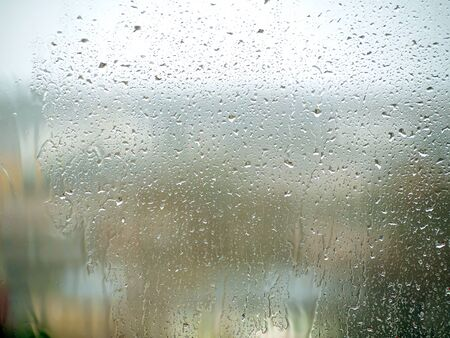 Rain drops on the glass in the spring afternoon. Close up of a window with rain drops falling down.The rain drops on household windows. Focus on rain drops. concept of sadness, frustration Stockfoto
