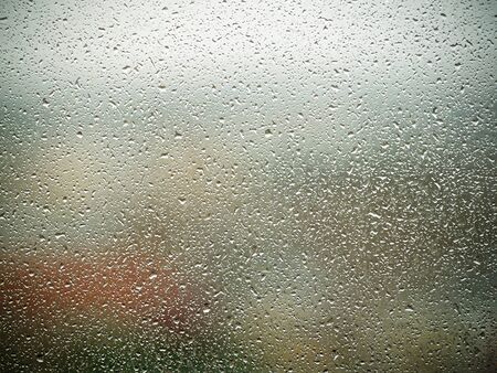 Rain drops on the glass in the spring afternoon. Close up of a window with rain drops falling down.The rain drops on household windows. Focus on rain drops. concept of sadness, frustration