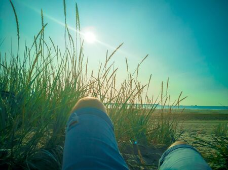 First-person view of a man relaxing, enjoying view over the beach with wild grasses. legs in jeans of hidden man lying behind a grass dune. Grass growing on the hill and sea surface. Vacation concept