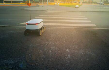 Two moving delivery robots on the street. crossing the road with a pedestrian crossing. Cyber-couriers are already cruising the sidewalks in Estoni. Copy space for design. Modern delivery concept