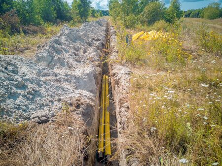 New pipeline of propylene on a background of green forest. Construction site of an overland pipeline. A long trench, dug out to drain the land and laying of pipes for communication Reklamní fotografie